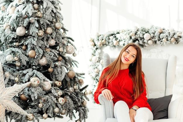 白い冬の色調のクリスマスの装飾と豪華なインテリアで笑っている長い暗いブロンドの髪を持つ魅力的な女性