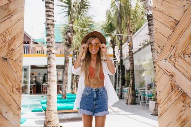Affascinante donna con acconciatura lunga che tocca i suoi occhiali da sole mentre posa al resort. colpo esterno di donna abbronzata felice in pantaloncini di jeans in piedi vicino a sedie a sdraio e sorridente.