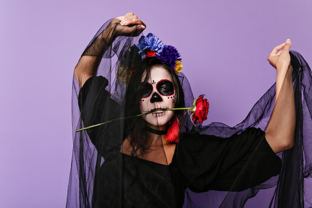 Charming woman with make-up in shape of skull is dancing with rose in her teeth. lady in halloween costume posing in lilac wall.