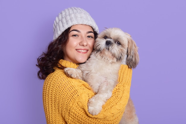 Charming woman with pekingese puppy, cuddles gently near face, wears knitted sweater and cap.