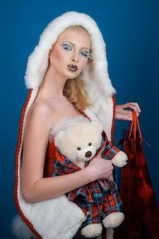 봉제 장난감과 빨간 가방을 손에 들고 전문 패션 메이크업을 한 매력적인 여성 산타 소녀
