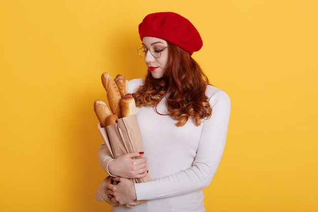 Charming woman with red hair, wears beret and white sweater, looks at long loaf in her head