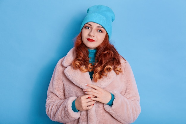 Charming woman with red hair, wears fashionable pink fur coat and cap