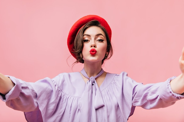Charming woman with red lips sends kiss. lady in beret makes selfie on pink background.