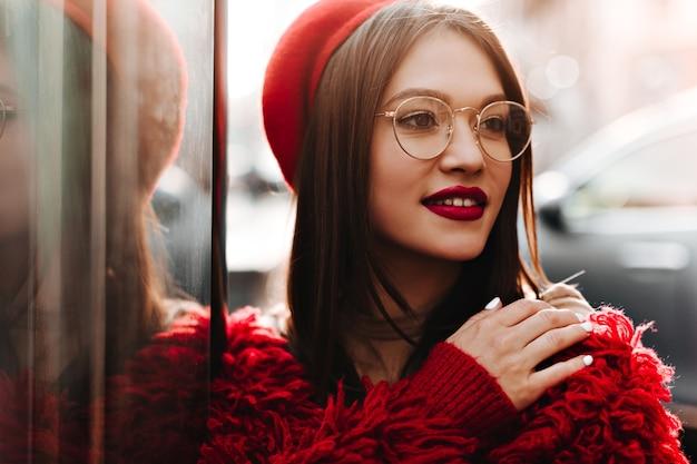 안경에 빨간 립스틱으로 매력적인 여자는 도시 주변을 산책합니다. 프랑스 스타일과 니트 코트에 베레모에 갈색 머리의 초상화.