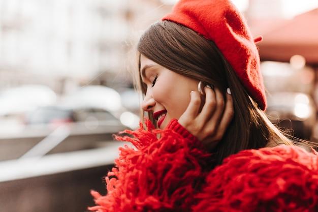 빨간 립스틱을 가진 매력적인 여자는 그녀의 눈을 감고 웃고 있습니다. 빨간색 따뜻한 옷을 입은 여자가 그녀의 은색 귀걸이를 만진다.