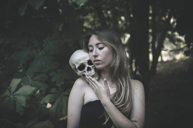 Charming woman with skull in thicket