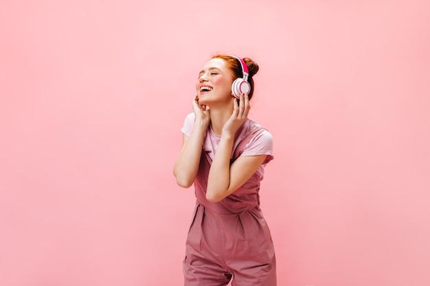 Affascinante donna con un sorriso esamina la macchina fotografica, tenendo lo smartphone nelle sue mani. donna in abito rosa ascoltando musica in cuffia.