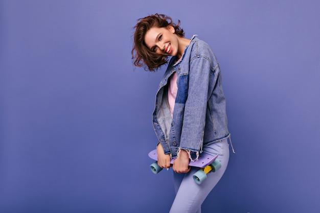 スケートボードで流行のヘアカットを持つ魅力的な女性。幸せな表情で笑っている素敵な女の子。
