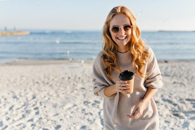 ビーチでお茶を飲むウェーブのかかった髪の魅力的な女性。ビーチで秋の日にリラックスしたセーターのスタイリッシュな女性。