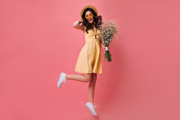 Charming woman in yellow dress jumps on pink wall and holds bouquet
