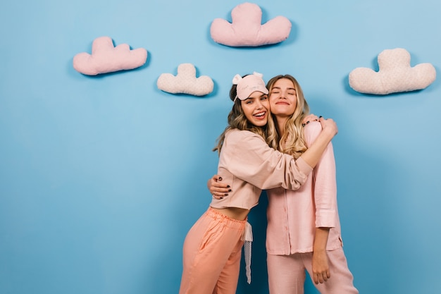 Charming women embracing on blue wall with clouds