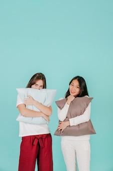 Charming women embracing pillows