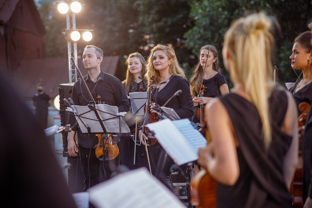 Charming women and man musicians holding violins and smiling while standing on outdoors stage