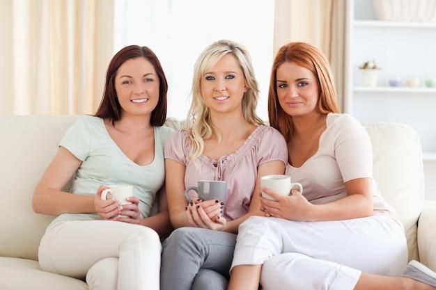 カップ、ソファーの上に座っている魅力的な女性