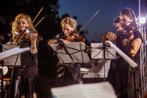 Charming women violinists looking at musical notes and playing melody on violin while performing outdoor concert under night sky
