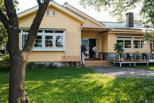 木製の窓と緑の芝生の庭のある魅力的な黄色の家
