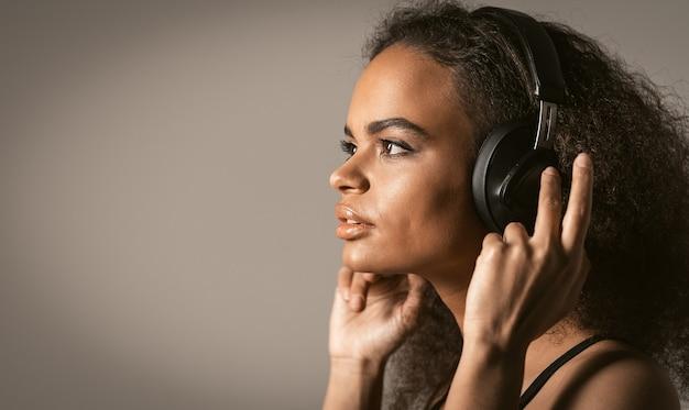 Очаровательная молодая афро-американская девушка слушает трек в наушниках