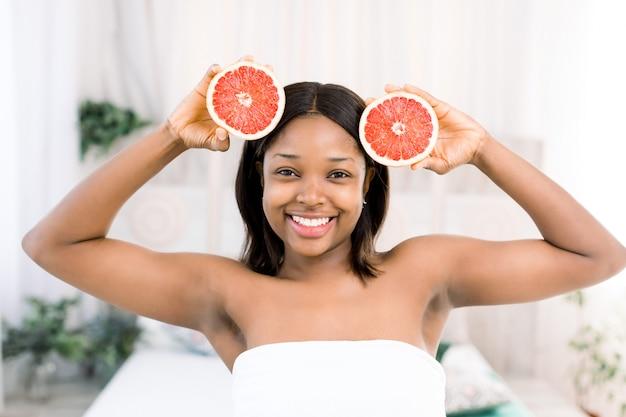 彼女の顔の前にグレープフルーツのスライスを保持している魅力的なアフリカの少女。明るい背景に分離されたアフリカ系アメリカ人の女性の笑顔の写真。美容スキンケアのコンセプト
