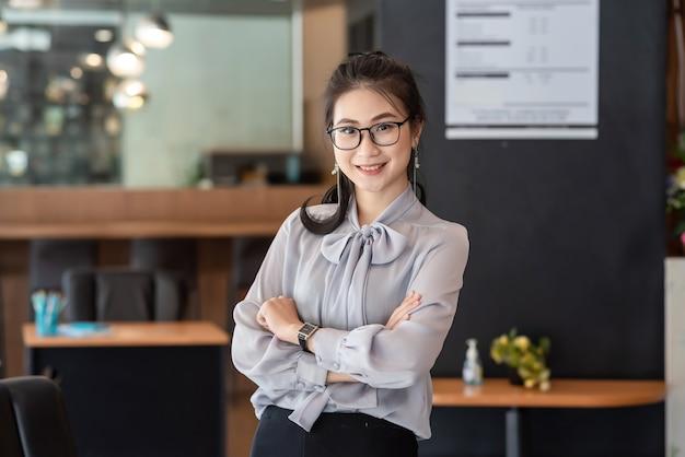 사무실에 서 매력적인 젊은 아시아 사업가. 카메라를 찾고 있습니다.