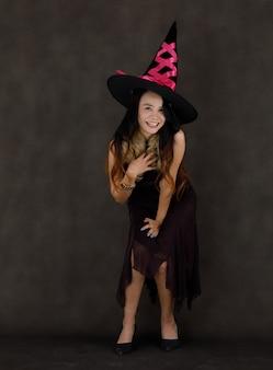 魔術師の衣装と帽子の笑顔と濃い灰色の背景にカメラを見て魅力的な若いアジアの女性