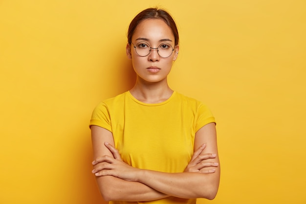 Charming young asian woman has fresh skin, looks  confidently, has serious expression, keeps hands crossed over chest, wears optical glasses and yellow t shirt, being deep in thoughts
