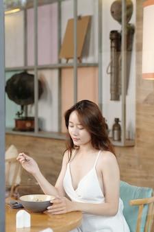 カフェで朝食にサラダの大きなボウルを持っている魅力的な若いアジアの女性