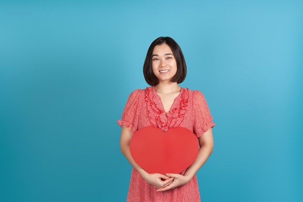 Charming young asian woman in a red dress holds a large red paper heart for valentine's day