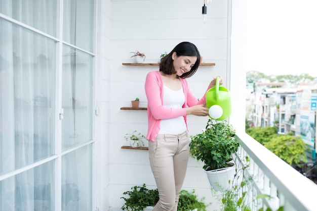Очаровательная молодая азиатская женщина поливает растение в контейнере на балконе в саду