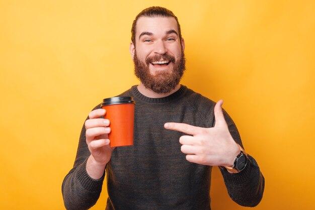 テイクアウトのために赤いコーヒーカップを指して魅力的な若いひげを生やした男