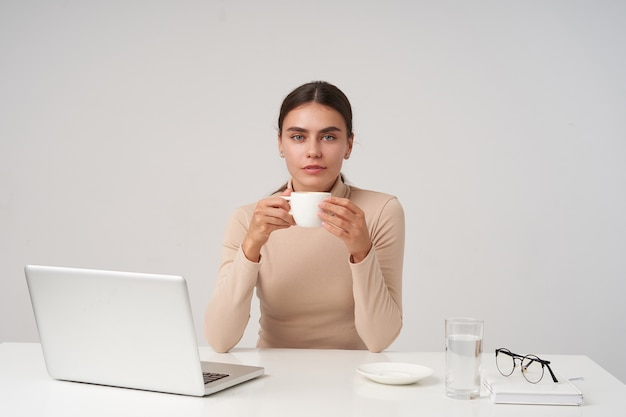 Charming young beautiful blue-eyed brunette lady holding cup of tea in raised hands and looking at camera with calm face, dressed in formal clothes while posing over white wall