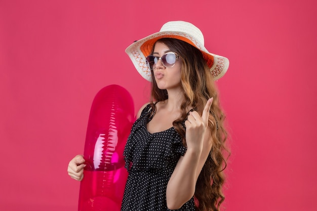 Charming young beautiful traveler girl in dress in polka dot in summer hat wearing sunglasses holding inflatable ring looking confident showing one finger and pointing up standing over pink bac