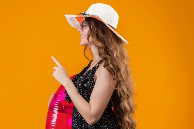 Charming young beautiful traveler girl in dress in polka dot in summer hat wearing sunglasses holding inflatable ring looking confident showing one finger and pointing up standing sideways over