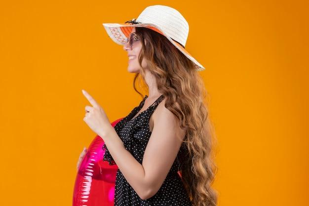 Очаровательная молодая красивая девушка-путешественница в платье в горошек в летней шляпе в солнцезащитных очках держит надувное кольцо, уверенно показывает пальцем и показывает вверх, стоя боком