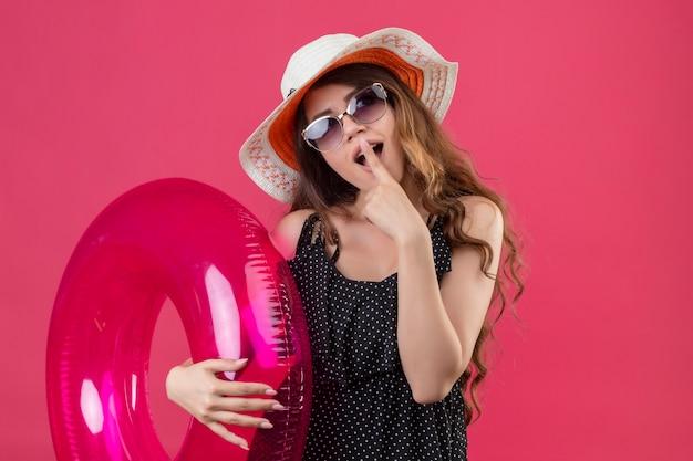Очаровательная молодая красивая девушка-путешественница в платье в горошек в летней шляпе в солнцезащитных очках с надувным кольцом, удивленная, с пальцем на губах, стоящим над розовым пространством