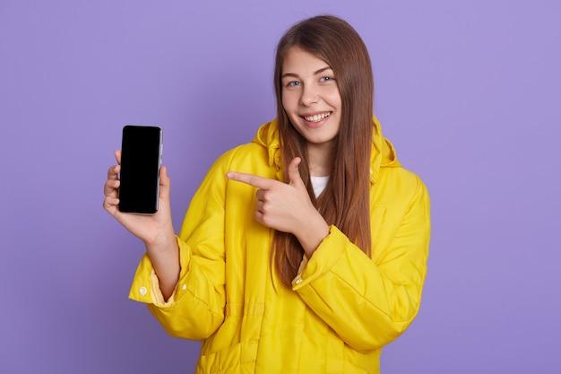 매력적인 젊은 아름 다운 여자 라일락 배경 위에 절연 포즈, 스마트 폰을 들고 빈 디스플레이, 웃 고, 광고에 대 한 공간을 복사 그녀의 앞 손가락으로 장치를 가리키는.