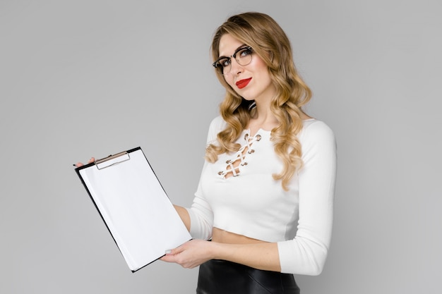 Charming young blond girl holding a sheet for notes