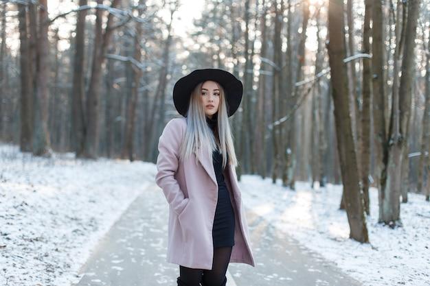 우아한 검은 모자에 검은 드레스에 세련된 라일락 코트에 매력적인 젊은 금발 여자는 겨울 맑은 날에 눈 덮인 숲에 서 있습니다. 예쁜 여자는 자연을 즐길 수 있습니다.
