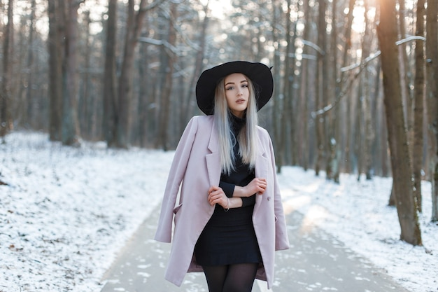 검은 유행 드레스에 분홍색 세련된 코트에 우아한 검은 모자에 매력적인 젊은 금발 여자가 겨울 숲에 서 있습니다. 아름다운 소녀는 풍경을 즐길 수 있습니다.