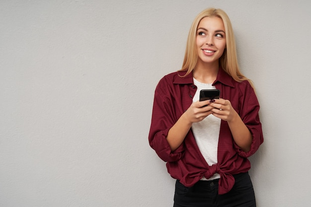 Charming young blonde female with long hair wearing burgundy shirt and white t-shirt while standing over light grey, holding mobile phone in raised hands and looking aside with gentle smile