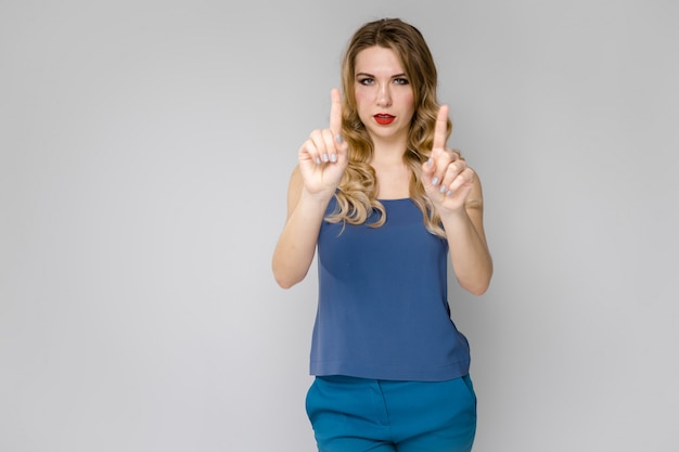 Charming young blonde girl in blue clothes showing gesture with her hands on gray background