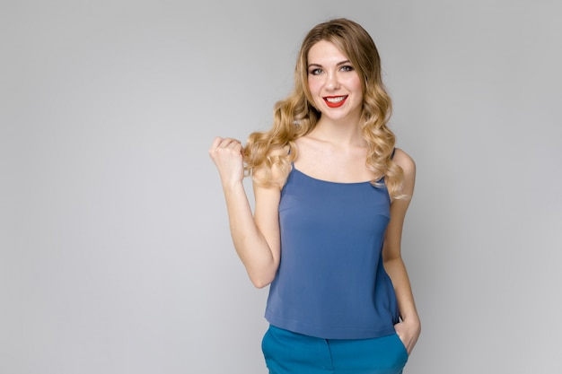 Charming young blonde girl in blue clothes smiling on gray wall