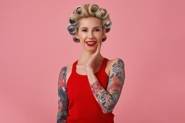 Очаровательная молодая блондинка татуированная женщина с вечерним макияжем делает прическу перед предстоящей вечеринкой, мягко трогая ее лицо и нежно улыбаясь в камеру, изолированные на розовом фоне