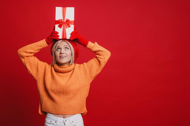 Очаровательная молодая блондинка женщина держит красную подарочную коробку на голове и пытается найти, чтобы угадать, что находится в изоляции на красном.