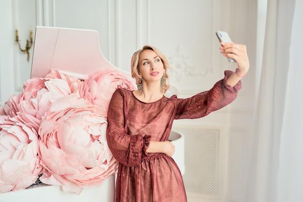 Очаровательная молодая блондинка в элегантном бордовом платье делает селфи на смартфоне
