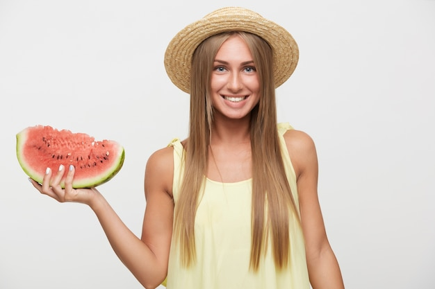 Charming young blue-eyed blonde lady with casual hairstyle being in nice mood and smiling cheerfully, keeping piece of watermelon in raised hand while standing over white background