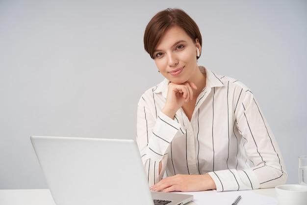 Affascinante giovane donna d'affari bruna dagli occhi marroni con taglio di capelli corto alla moda sorridente delicatamente e appoggiando la testa sulla mano sollevata mentre è seduto su bianco