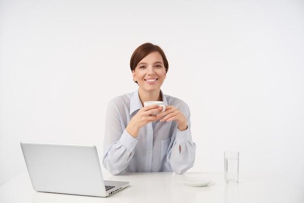 Очаровательная молодая кареглазая дама с короткими волосами держит чашку кофе в поднятых руках и весело смотрит с приятной улыбкой, работая в современном офисе с ноутбуком