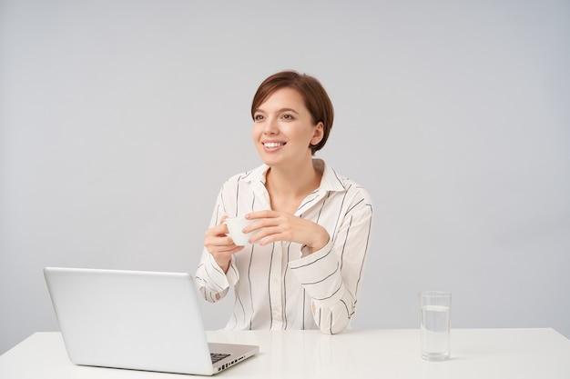 Affascinante giovane donna dai capelli corti dagli occhi marroni vestita in abiti formali tenendo la tazza di tè nelle mani alzate e guardando positivamente davanti a sé con un sorriso piacevole, posa su bianco