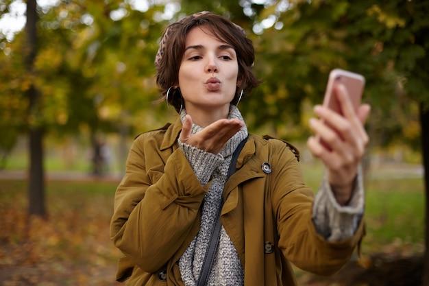 Affascinante giovane signora bruna dai capelli castani con trucco naturale piegando le labbra in un bacio d'aria e mantenendo il palmo sollevato mentre fa selfie con il suo telefono cellulare, in posa all'aperto in una calda giornata autunnale